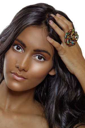 beautiful tanned woman with natural make-up and long curly hair wearing a large ring. Stock Photo