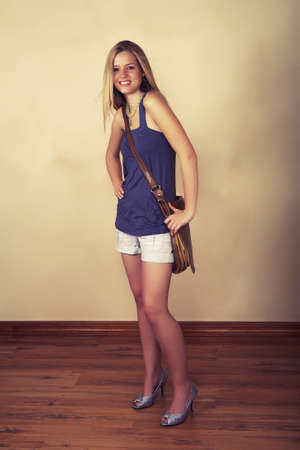 Full length of a charming young woman smiling with long blond hair and holding a large student bag against grunge wall on wooden floor photo