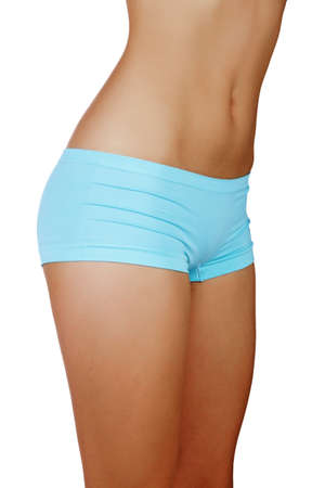 waist up: stomach and of a young fit woman with tanned skin and thin waist in blue panties.