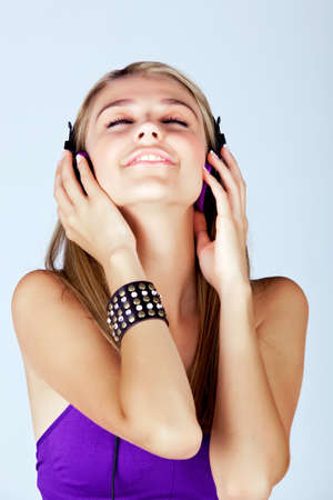 beautiful young blond woman listening to music in headphones wearing purple top and leather fashion cuff on studio background photo