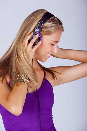 beautiful young blond woman listening to music in headphones wearing purple top and leather fashion cuff on studio background Stock Photo - 14683797