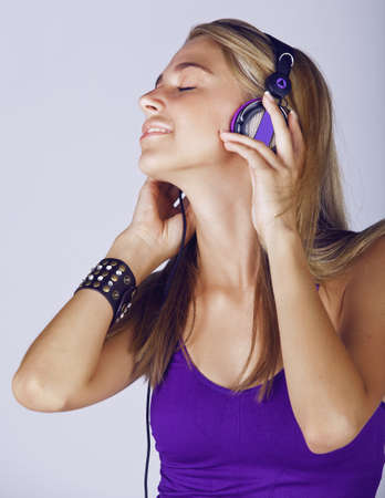 cuff bracelet: beautiful young blond woman listening to music in headphones wearing purple top and leather fashion cuff on studio background