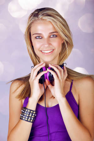 beautiful young blond woman listening to music in headphones wearing purple top and leather fashion cuff on studio background Stock Photo - 14683799