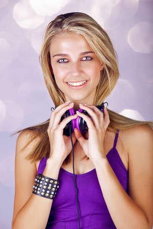 belle jeune femme blonde l'écoute de musique dans les écouteurs porter haut violet et le brassard en cuir de mode sur fond de studio Banque d'images