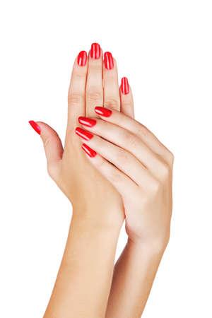 Gros plan sur les mains d'une jeune femme avec manucure rouge sur les ongles à long contre un fond blanc Banque d'images