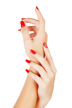 closeup of hands of a young woman with long red manicure on nails against white background