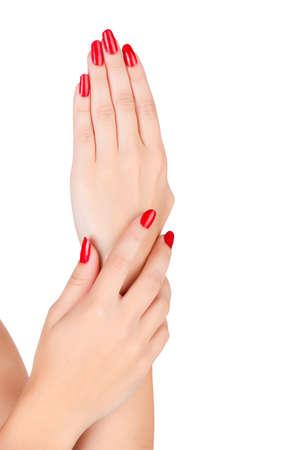 Gros plan sur les mains d'une jeune femme avec manucure rouge sur les ongles à long contre un fond blanc Banque d'images - 13819896