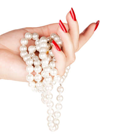 beautiful hand of a young woman with red manicure holding white pearl necklace on white background Stock Photo