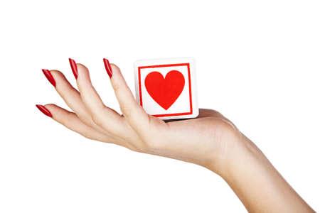 uñas pintadas: closeup mujer joven s mano con largas uñas rojas sosteniendo bloque con el corazón rojo