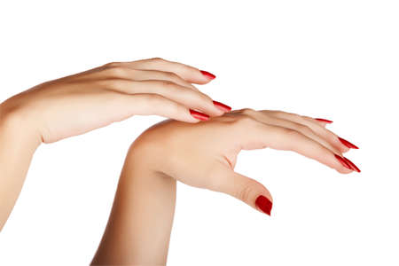 closeup of hands of a young woman with long red manicure on nails against white background Stock Photo - 13819846