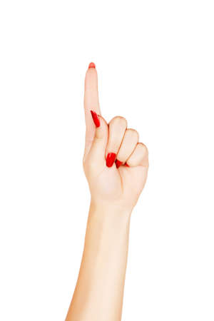 uñas largas: close-up de la mano de la mujer con las uñas de color rojo apuntando con el dedo índice sobre fondo blanco