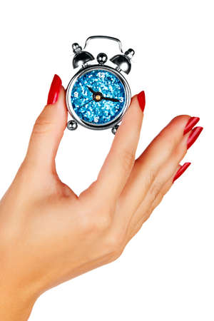 beautiful hand of a young woman with red manicure holding a blue alarm clock on white background Stock Photo - 13819958