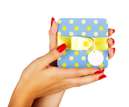 beautiful hands of a young woman with red manicure holding a blue gift box with yellow ribbon photo