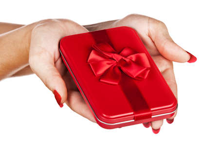 beautiful hands of a young woman with red manicure holding a red tin gift box with red ribbon photo