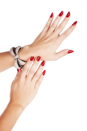 closeup hands of young woman with red manicure polished nails wearing diamante bow bracelet photo