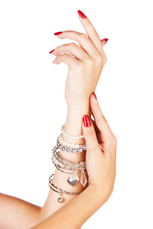 closeup hands of young woman with red manicure polished nails wearing many silver bangles and pearl bracelets photo