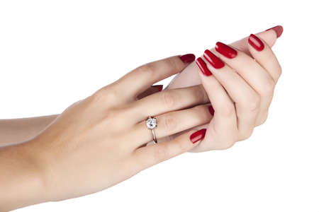 närbild händerna på ung kvinna med rött manikyr polerade naglar bär en dyr förlovningsring med en diamant Stockfoto