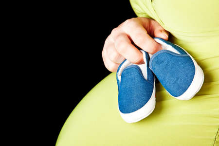 baby bump: young expecting woman in green holding blue baby shoes across her pregnant stomach