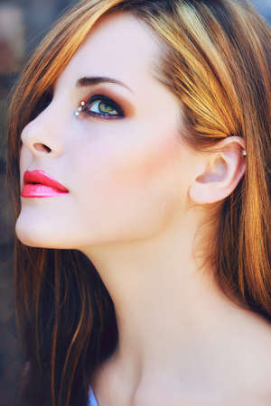 studs: portrait of a beautiful young woman with long brown hair and artistic make-up with pink lips
