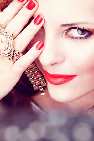 face of a beautiful young woman with bright pink lipstick and glitter nailpolish holding a watch with a smile