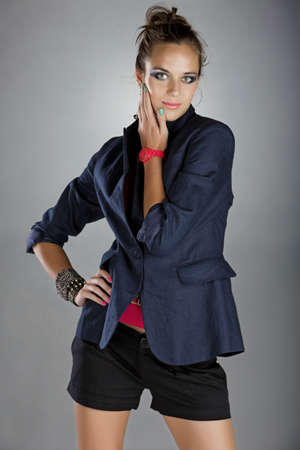 beautiful  young woman with dramatic make-up and green pink manicure wearing shorts, dark navy blue linen jacket and pink neon watch on gray background photo