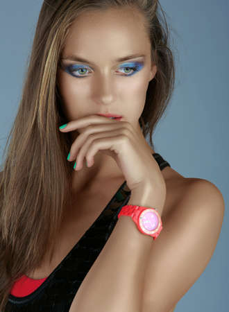 portrait of a beautiful tanned woman with dramatic eyeshadow and green manicure wearing pink neon watch  Stock Photo