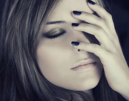 closeup portrait of beautiful young woman with dark blue nails touching sad face with closed eyes.
