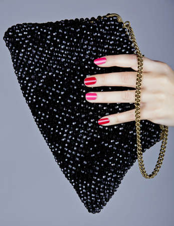 hand of a young woman with bright fashion manicure with pink and red nails holding a vintage beaded bag. photo