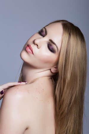 belle femme avec fard à paupières violet sur les yeux fermés et de longs cheveux blonds sur son épaule contre le fond de studio bleu