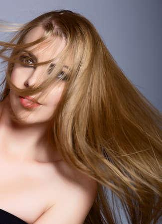 belle femme avec de longs cheveux blonds qui souffle sur son visage contre le fond de studio bleu. Banque d'images