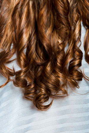 blond streaks: long curly professionally dyed red hair on silver background