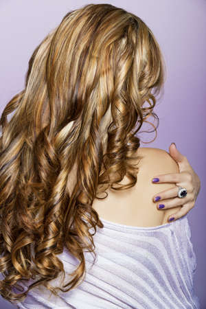 beautiful woman with long blond professionally dyed curly hair touching wearing purple manicure on purple background. photo