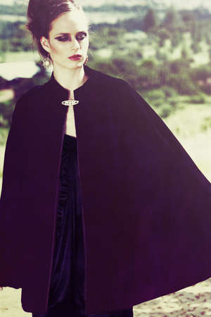 beautiful woman with grunge dramatic makeup outside wearing vintage velvet cape and expensive jewelry. photo