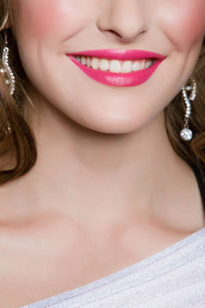 young woman wearing bright pink lipstick smiling in closeup portrait. photo