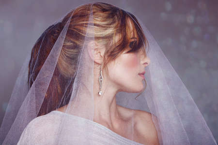 belle mariée portait robe hors épaule et aux cheveux en queue de cheval portant le voile sur le fond mousseux bokeh
