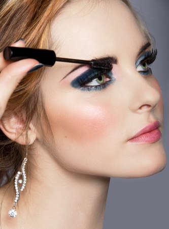 portrait of beautiful woman with smoky blue eyeshadow and long false eyelashes applying mascara with a wand