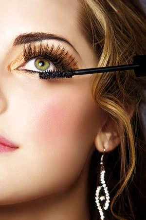 Porträtt av vacker kvinna med rökig guld ögonskugga och långa lösögonfransar ansöker mascara med en trollstav