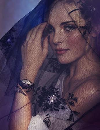 portrait of romantic beautiful woman wearing black veil and wings bracelet on purple background.