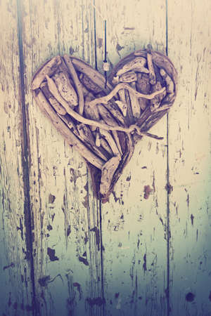 driftwood: old heart made of driftwood on vintage wood wall background. Stock Photo