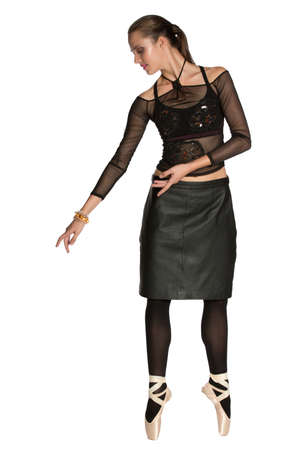 beautiful woman wearing a mesh fashion top and a leather black skirt dancing on ballet point shoes over white background.
