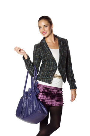 beautiful young woman posing in white top, green tweed jacket and purple mini skirt and leather bag over white background   photo