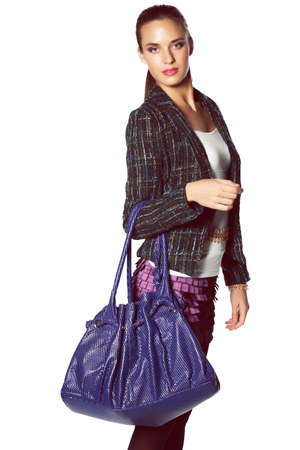 beautiful young woman posing in white top, green tweed jacket and purple mini skirt and leather bag over white background. photo