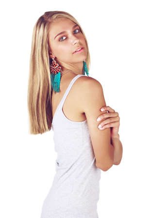 beautiful tanned young woman with blond hair wearing a summer dress and coral and blue feather earrings on white studio background photo