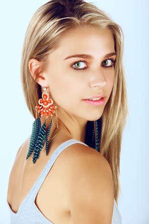 belle femme bronzée jeune avec des cheveux blonds vêtue d'une robe d'été et boucles d'oreilles plumes de corail et bleu sur fond de studio Banque d'images