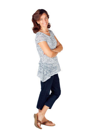 Beautiful young woman in her 30s standing with her hands folded against white background and wearing top with stripes and jeans photo