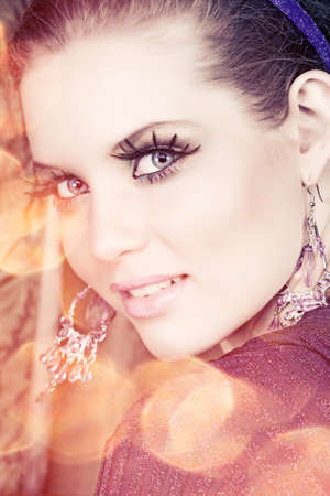 portrait of a beautiful woman with long false feather eyelashes and bright make-up on golden lights background  photo