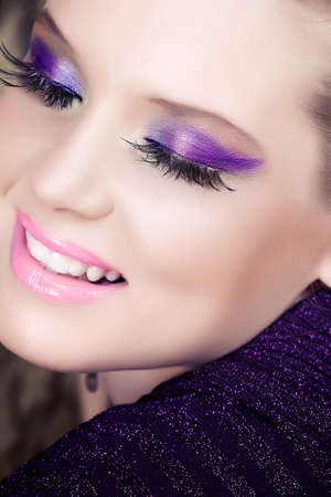 closeup portrait de femme souriante belle avec de longs cils et des paupières métalliques violettes pourpres