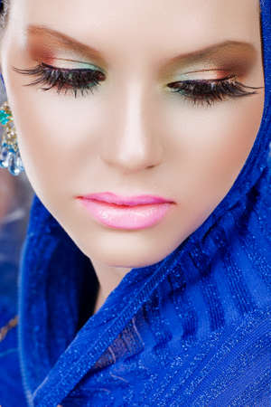 portrait of a beautiful woman with long false feather eyelashes and bright make-up wearing blue photo