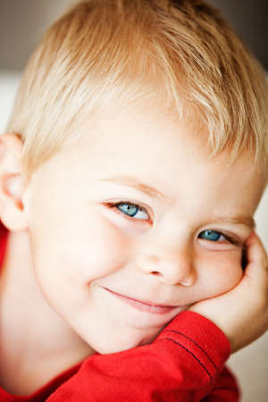 happy cute toddler boy with blue eyes and blond hair making faces - shallow depth of field, focus on the eyes photo