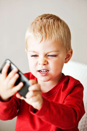 upset little 3 year old boy is frustrated with the media player or electronic toy he is holding photo